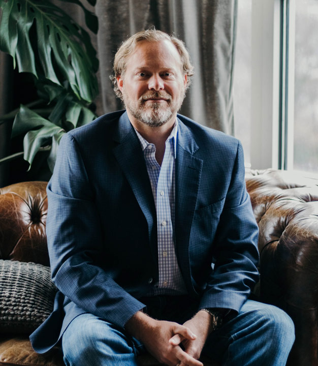 Commercial real estate broker sitting on leather couch in blazer in Equitable Property Company offices in Nashville, Tennessee
