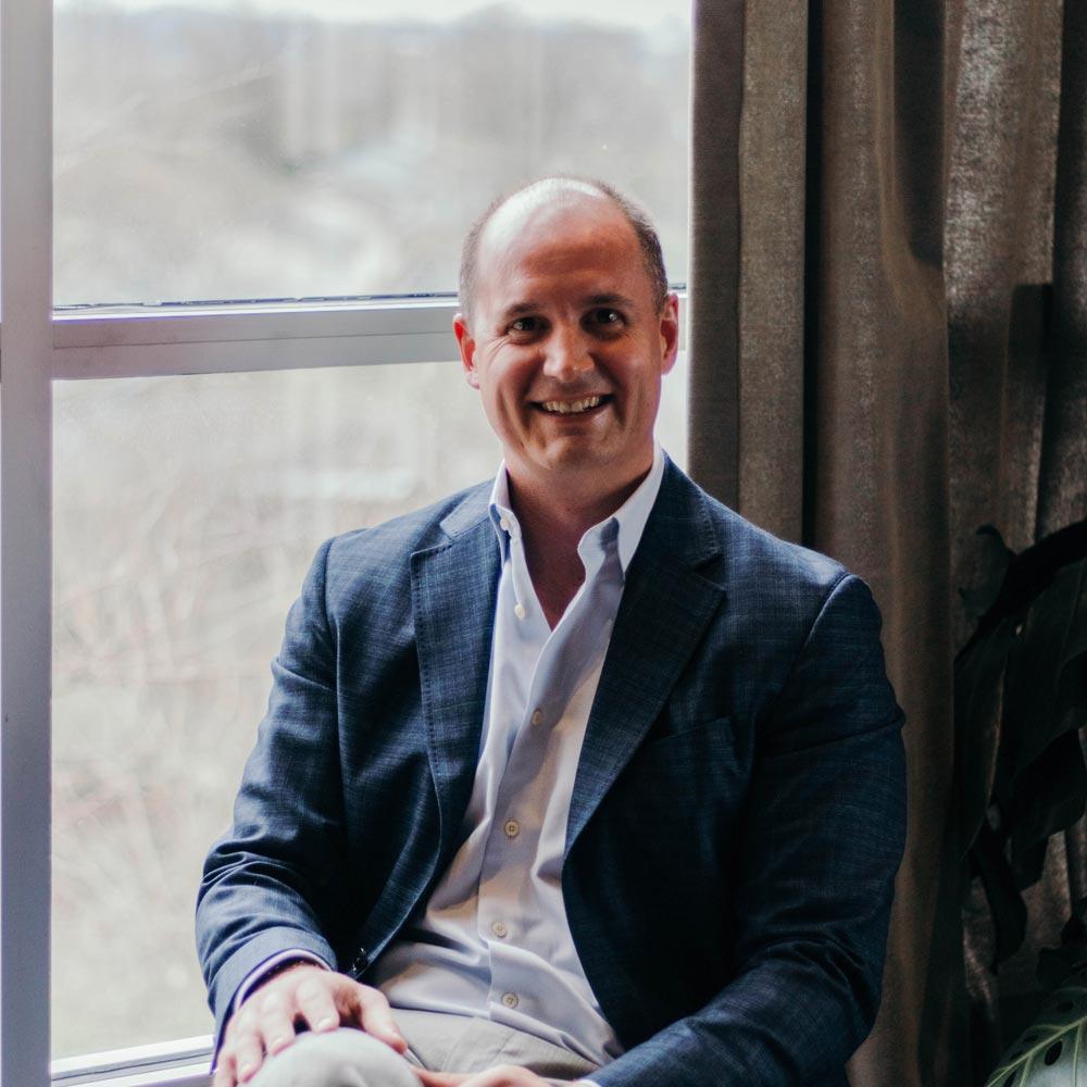 Man in blazer sitting in front of glass window