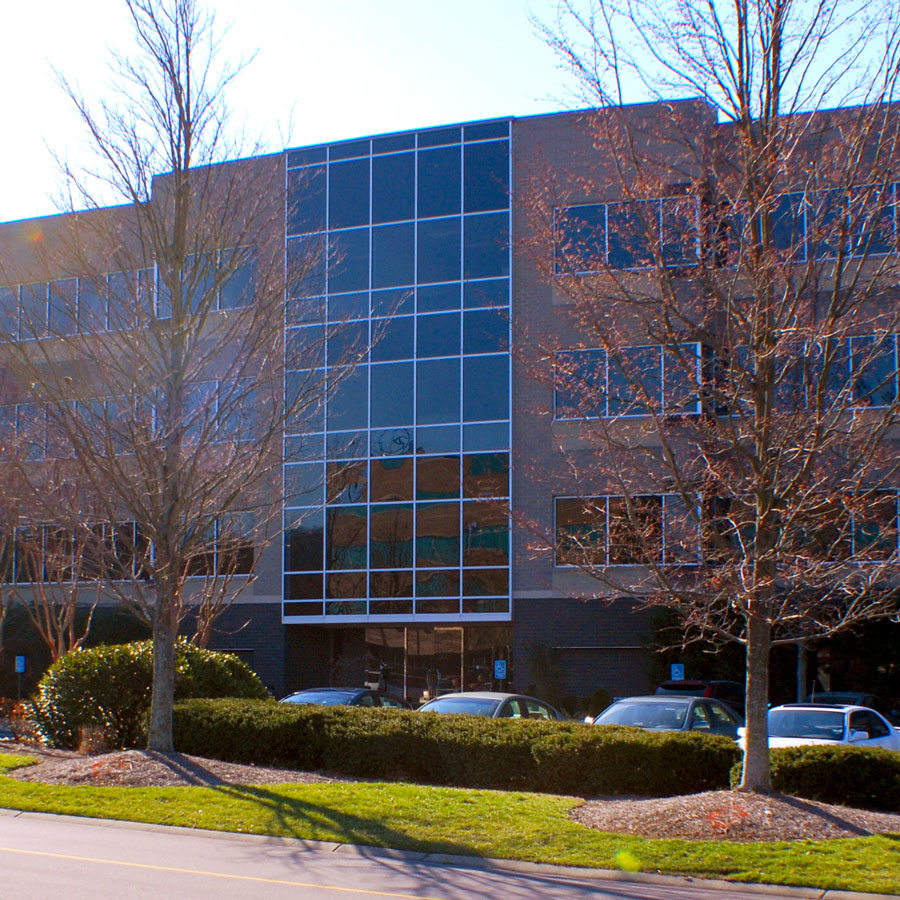 Large office building with glass windows covering the front available for lease